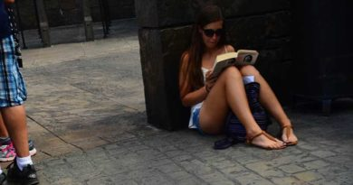 creepshot of a girl wearing shorts reading a book